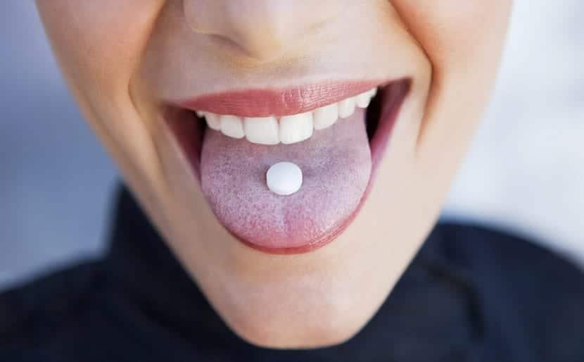 Chica tomando pastillas anticonceptivas