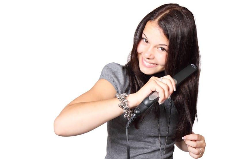 Chica usando plancha del pelo