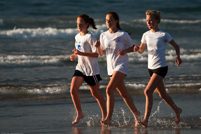Three high school girls, as part of a larger group, run up and d