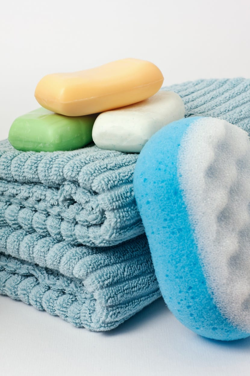 Three soap bars, a green, white and orange one, on two blue towels folded a couple of times. Next to those there's a two sided bathing massage sponge. The towels are made from a thick soft fabric with a line pattern.