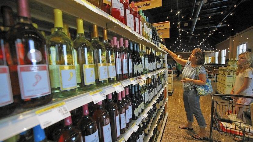 Mujer buscando una botella de vino en un supermercado