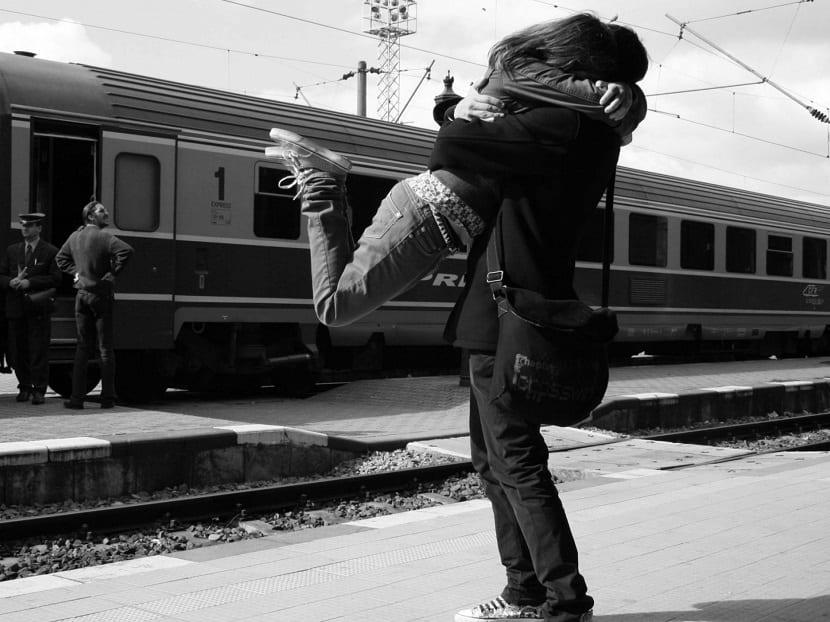Pareja besándose en una estación de tren