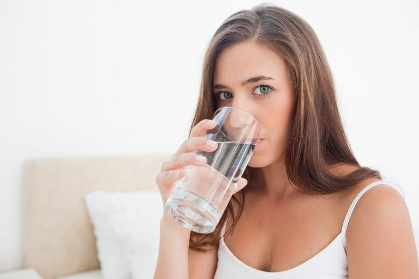 Chica bebiendo agua al levantarse