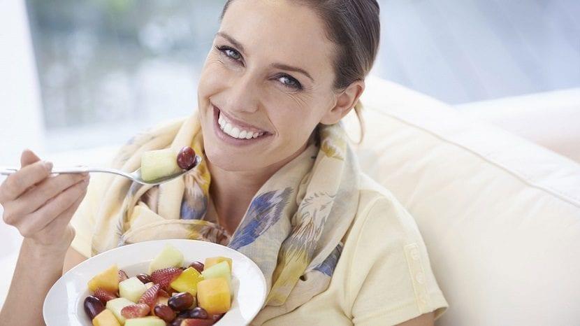 Mujer tomando desayuno que aporta energía