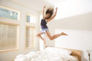 Chica saltando sobre la cama