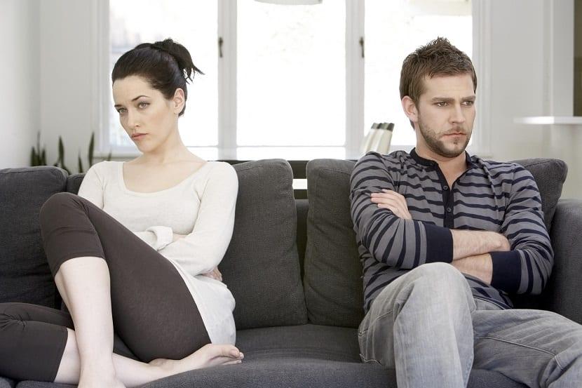 Pareja enfadada sentada en un sofá