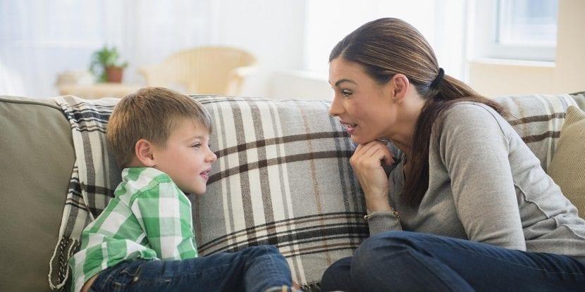 Madre dialogando con su hijo sin gritos en el sofá
