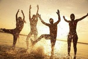 Grupo de amigos saltando en la orilla de la playa