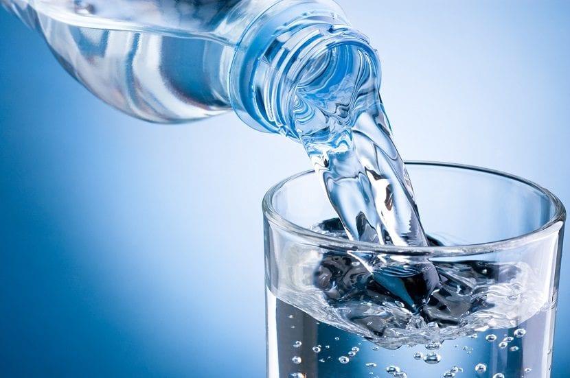 Botella virtiendo agua en un vaso