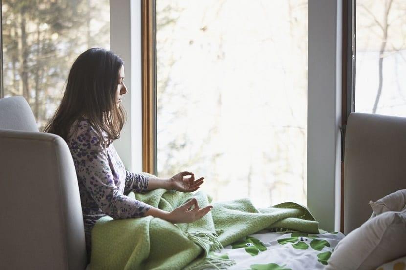 Chica joven meditando en casa