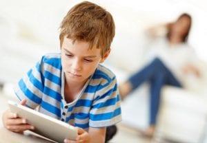 Niño con una tablet y la madre sentada detrás