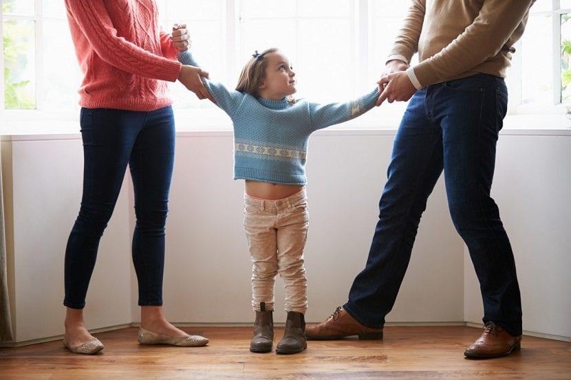 Padres tirando cada uno de la mano de su hija