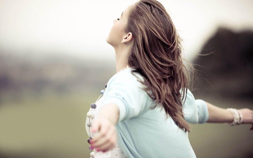 Mujer extendiendo los brazos al aire libre