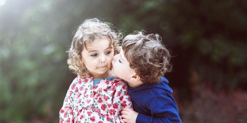 Niño dando un beso en la mejilla a una niña
