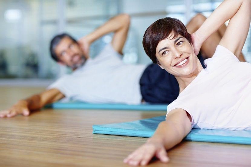 Mujer y hombre por detrás haciendo ejercicio en un gimnasio