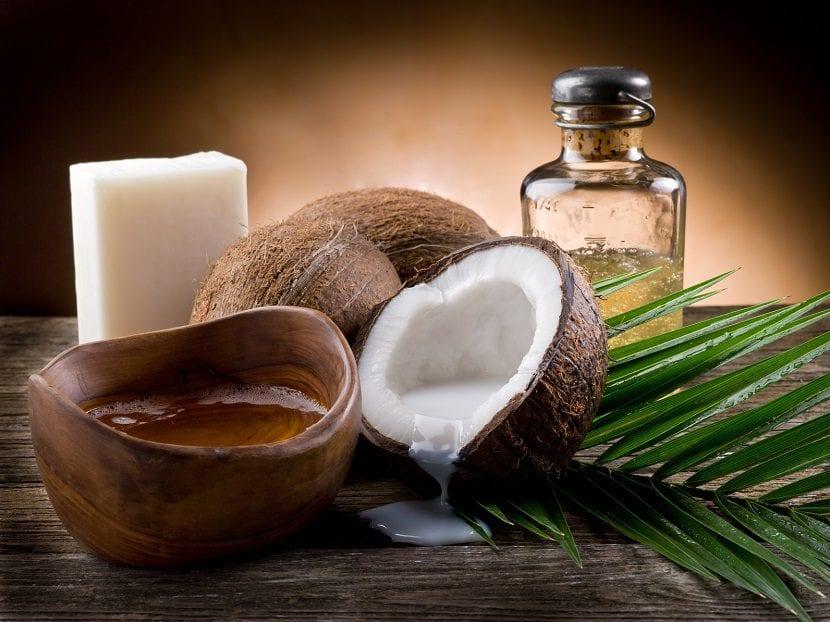 Aceite de coco junto a un coco partido por la mitad y una rama de una palmera
