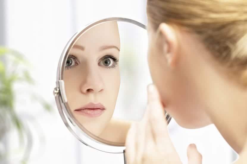 Chica mirando en un espejo los puntos negros de la cara