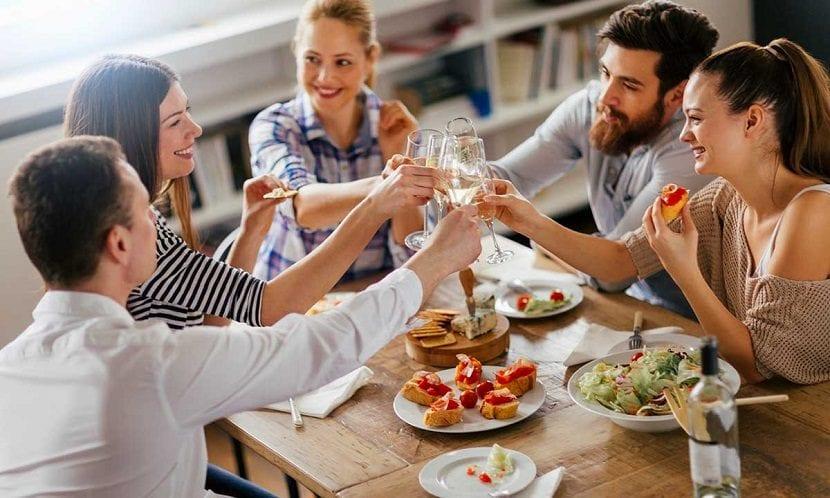 Grupo de amigos brindando y comiendo