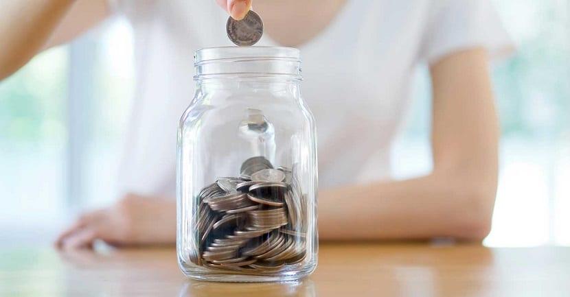 Mujer metiendo una moneda en un tarro de cristal