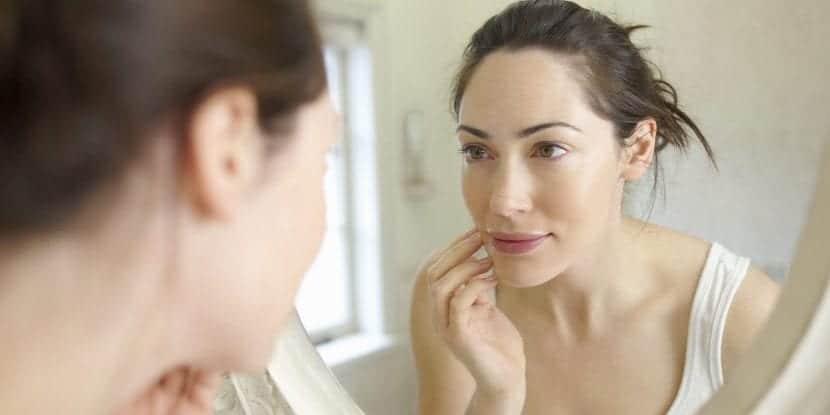 Mujer mirándose al espejo y tocando su cara