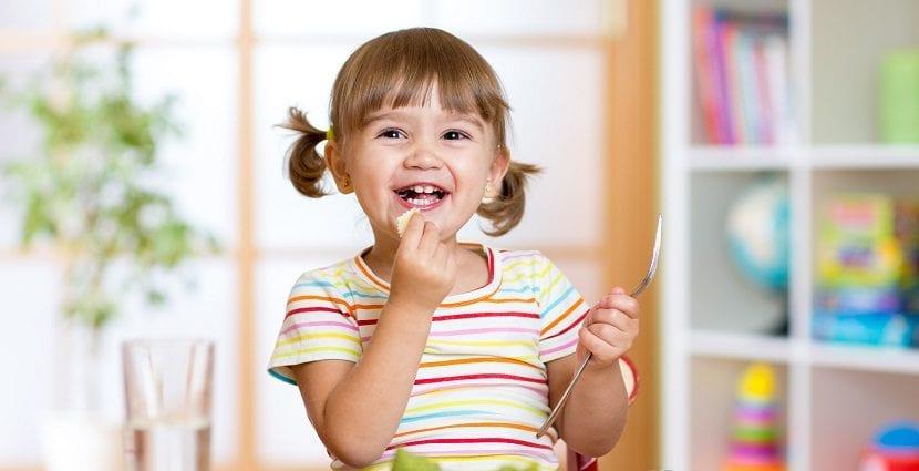 Niña sonriente con coletas comiendo