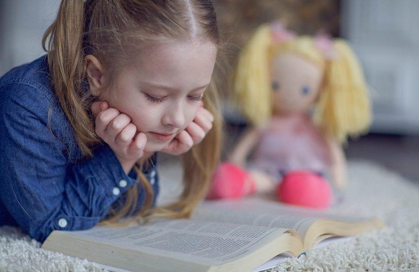 Niña leyendo sobre la cama al lado de una muñeca