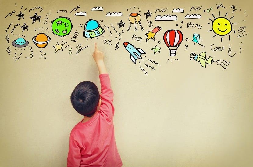 Niños con altas capacidades señalando dibujos en una pared