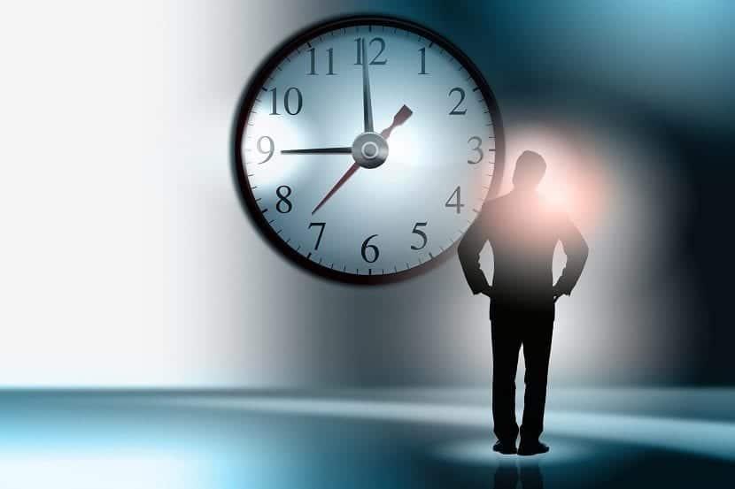Hombre delante de un reloj de pared gigante
