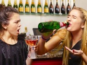Dos chicas adolescentes bebiendo de una botella y de una copa