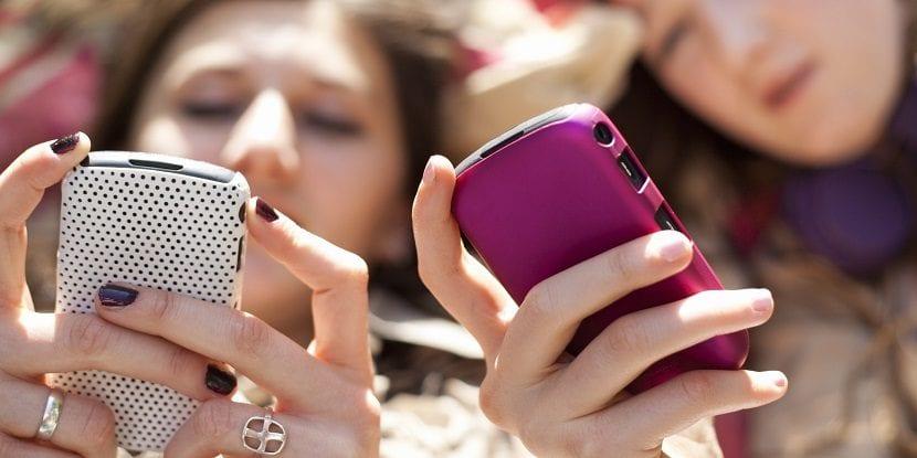 Adolescentes usando sus móviles