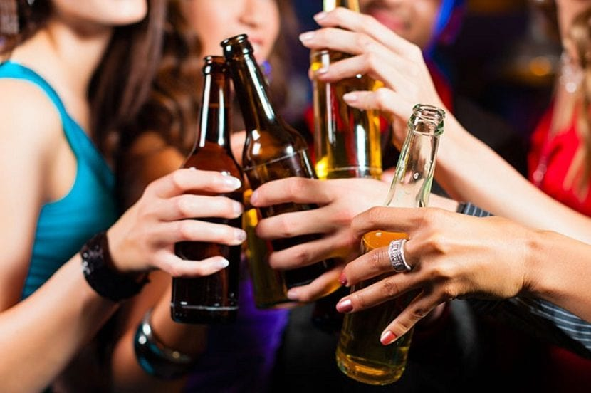 Manos de un grupo de chicas sosteniendo botellas de cerveza