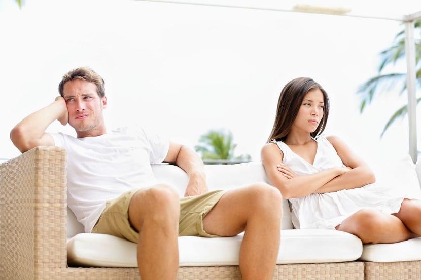 Pareja enfadada sentados en un sofá