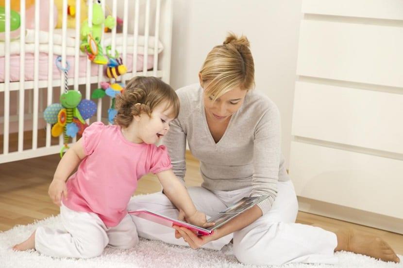 Madre fomentando el aprendizaje de su bebé con un libro