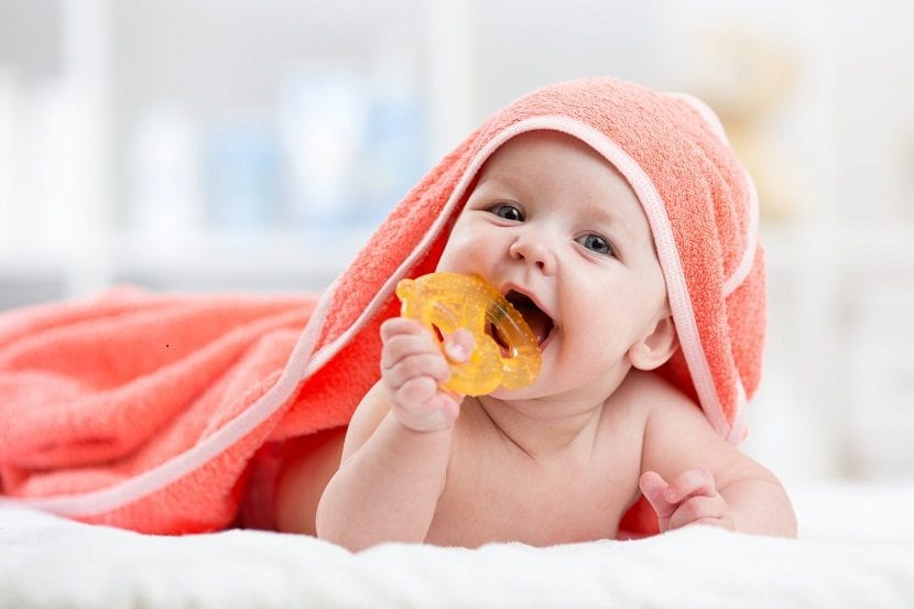 Bebé con una toalla roja mordiendo un juguete