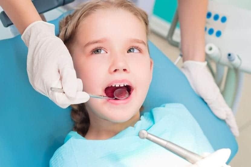 nena que mira al dentista en la consulta