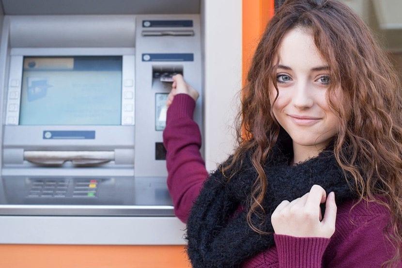 chica adolescente con tarjeta en el cajero