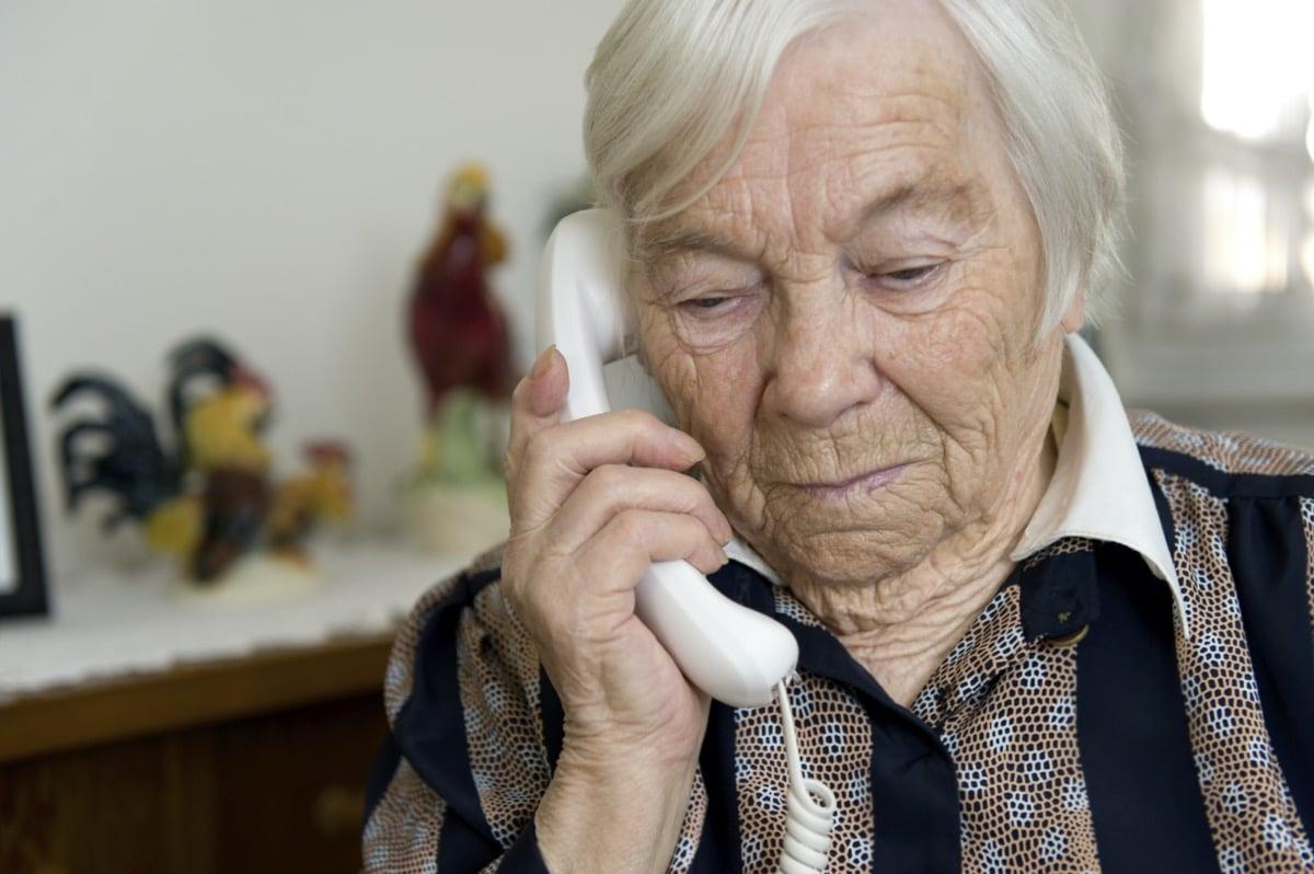Abuela usando un teléfono fijo
