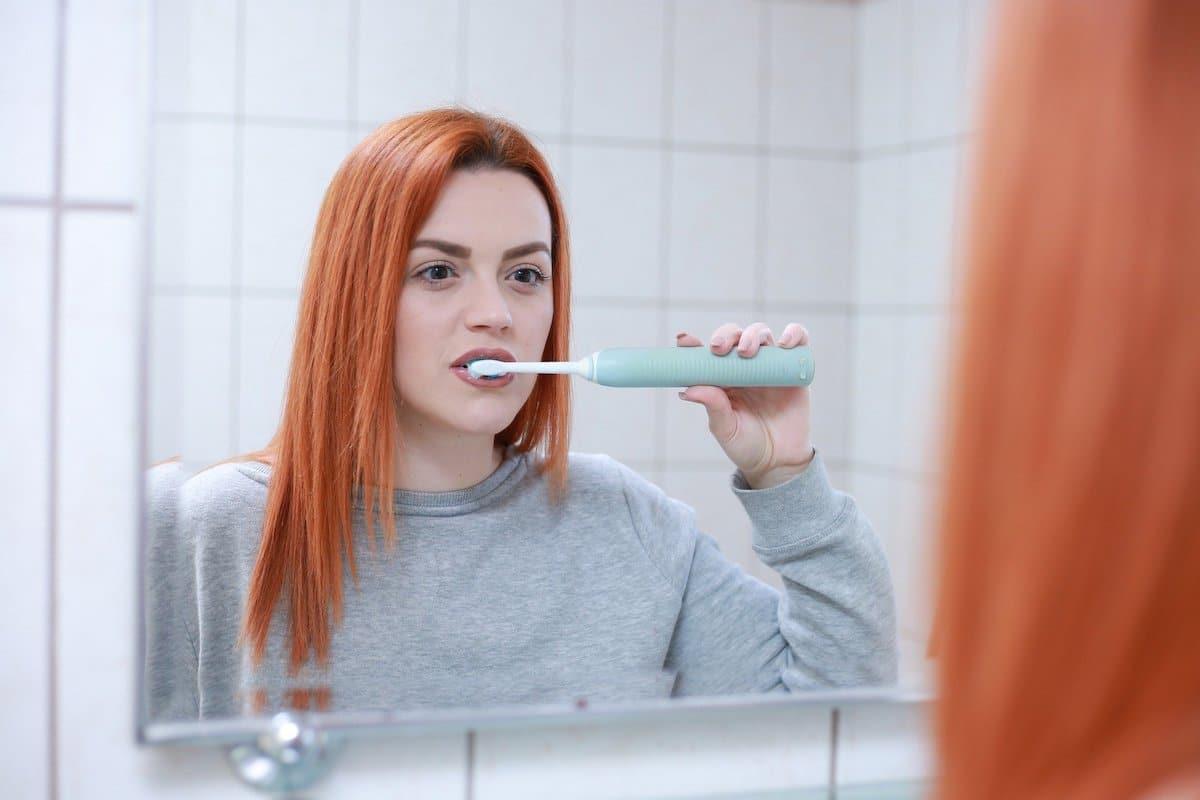 Chica se cepilla los dientes para tener los dientes más blancos.