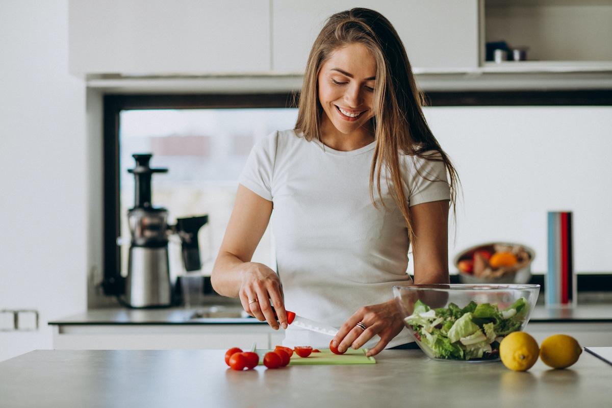 Chica cocinando comida saludable.