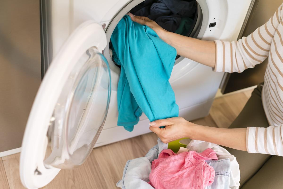 Lavar la ropa en lavadora en casa.